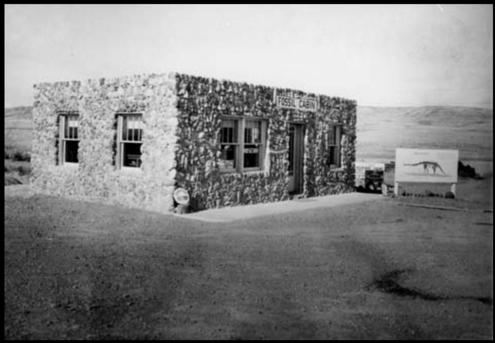 """Como Bluffs, Wyoming – Front Exterior of Fossil Cabin and Sign with a Dinosaur on it"""